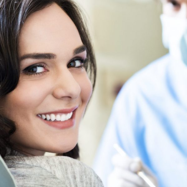 Smiling young woman receiving dental checkup